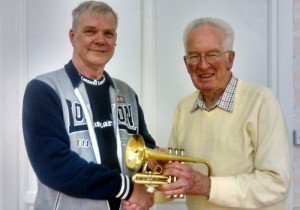 MD John Powell (left) accepts the cornet from John Sargant
